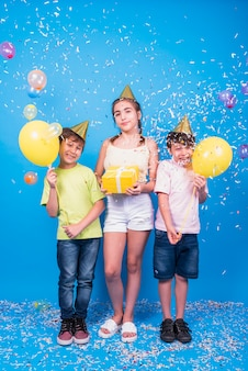 Des amis souriants fêtent leur anniversaire avec un cadeau; des ballons; et confettis sur fond bleu