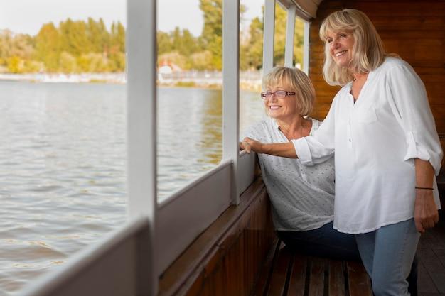 Amis souriants de plan moyen sur le bateau