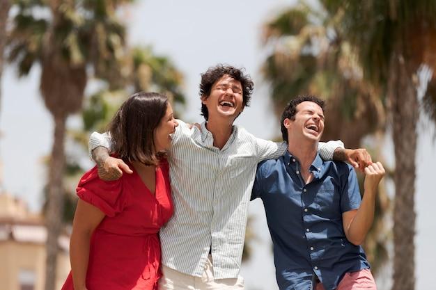 Amis souriants de plan moyen à l'extérieur