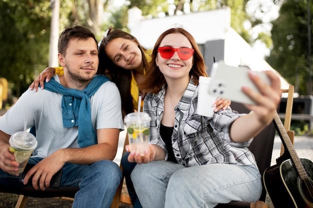 Amis souriants de plan moyen prenant un selfie