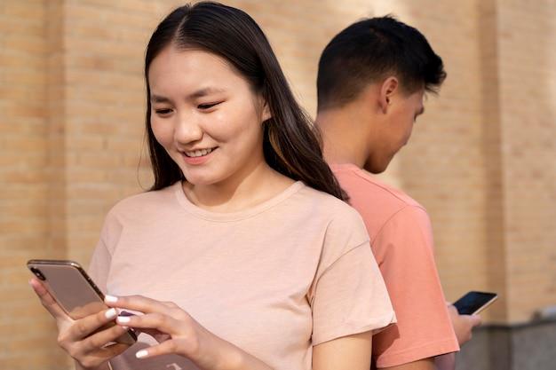 Amis souriants de plan moyen avec des téléphones