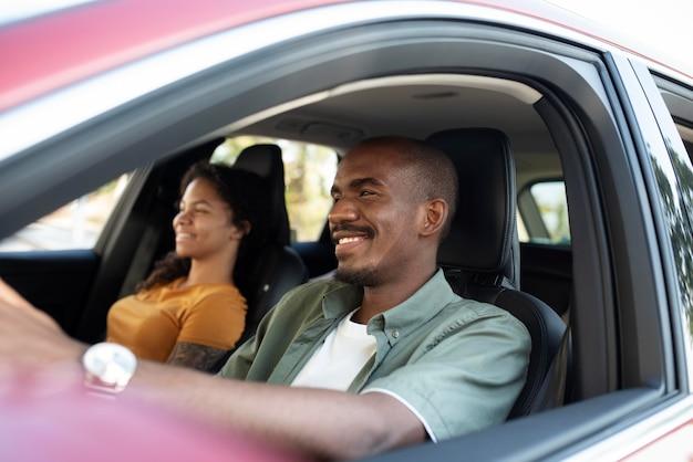 Amis souriants de plan moyen voyageant en voiture
