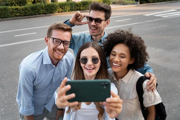 Amis souriants prenant un selfie ensemble à l'extérieur