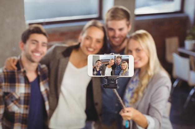 Amis souriants prenant selfies avec selfiestick