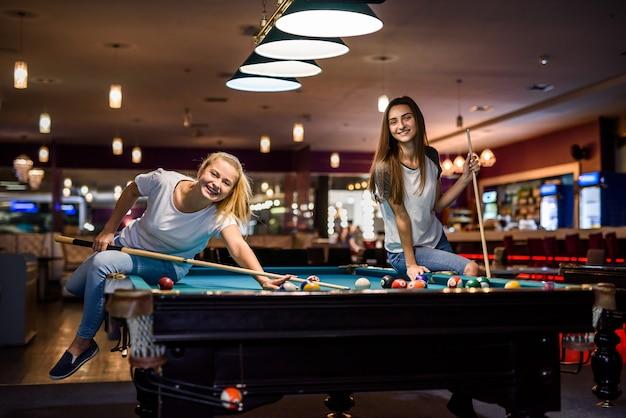 Amis souriants avec des queues jouant au billard dans un pub
