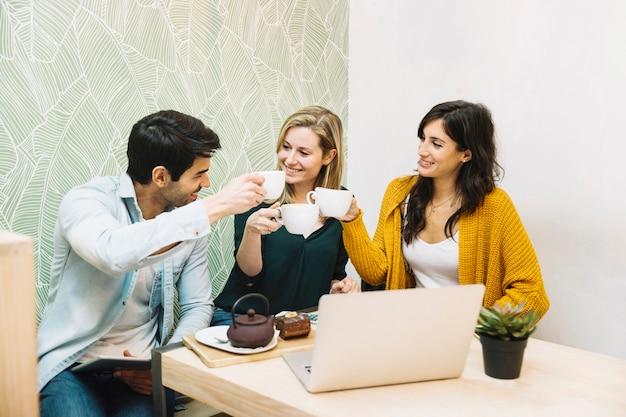 Amis souriants tinter des tasses de thé