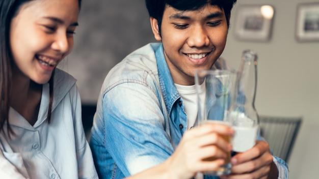 Des amis sourient, font la fête au bar, discutent et clochent des bouteilles de boissons.