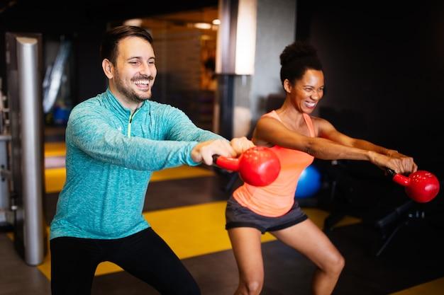 Des amis sportifs attrayants s'entraînent dans une salle de sport
