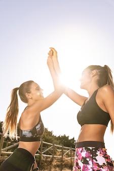 Amis sportifs à faible angle faisant un high five