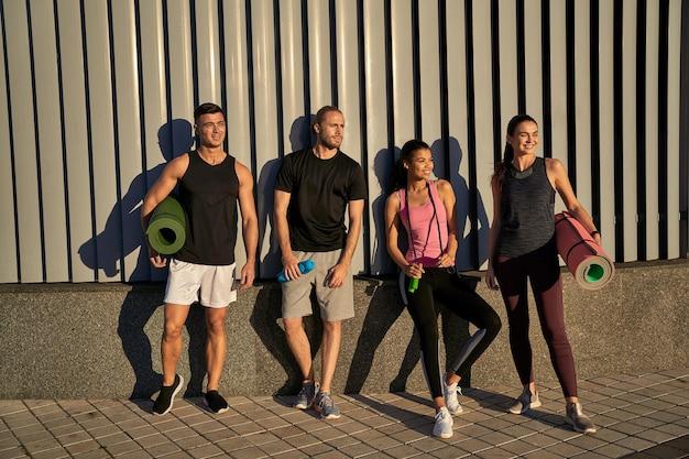 Amis sportifs heureux posant près du mur en plein air