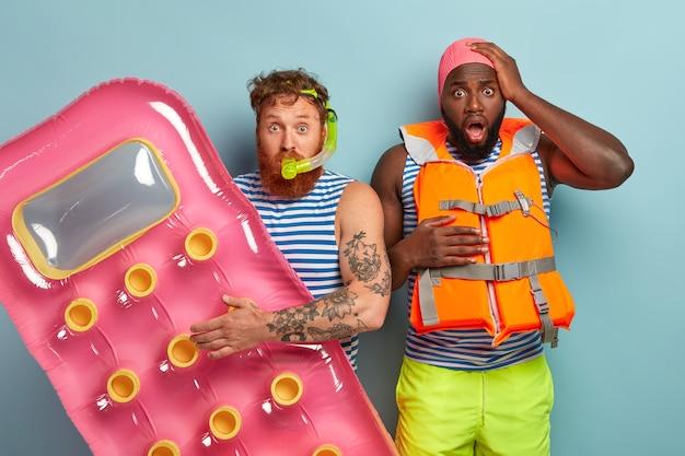 Amis stupéfaits posant avec des articles de plage