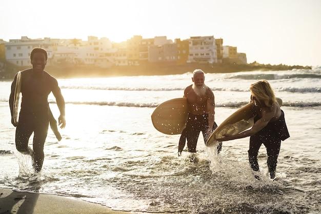 Amis surfeurs multigénérationnels s'amusant en surfant sur la plage - mise au point douce sur l'homme droit
