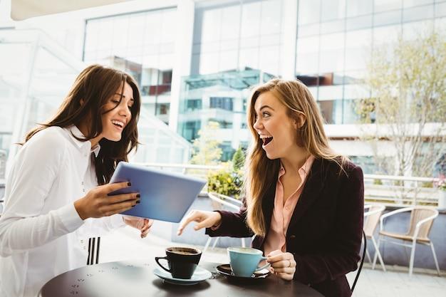 Amis surpris en regardant tablette au café