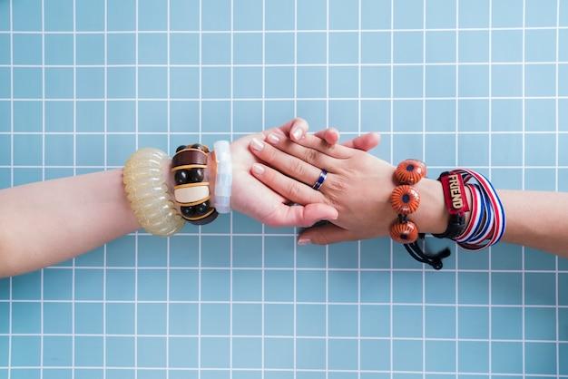 Amis tenant par la main avec des bracelets
