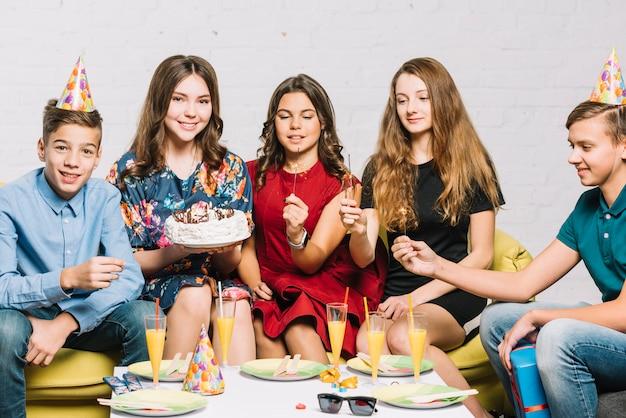 Amis tenant des pétards dans la main assis avec une fille d'anniversaire tenant un gâteau dans la main