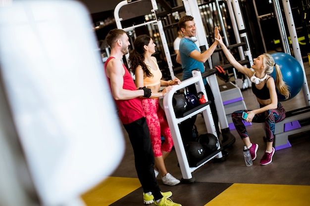 Amis en tenue de sport discutant ensemble dans une salle de sport après une séance d'entraînement