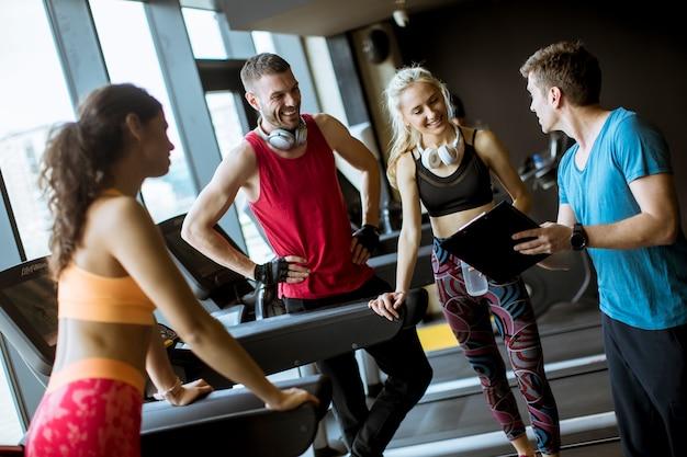 Amis en tenue de sport discutant et riant ensemble pendant qu'ils se reposaient dans la salle de sport après une séance d'entraînement
