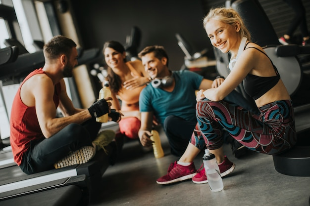 Amis en tenue de sport discutant et riant ensemble tout en se reposant dans la salle de sport après une séance d'entraînement