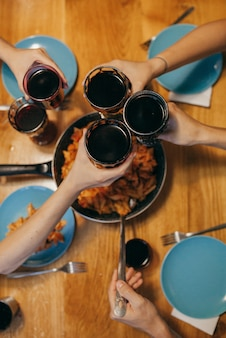 Amis en train de dîner avec du vin rouge