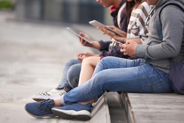 Amis utilisant des appareils à l'extérieur