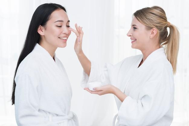 Amis utilisant une crème de beauté dans un spa