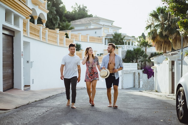 Amis en vacances d'été, riant, s'amusant, sautant, marchant dans les rues de la ville
