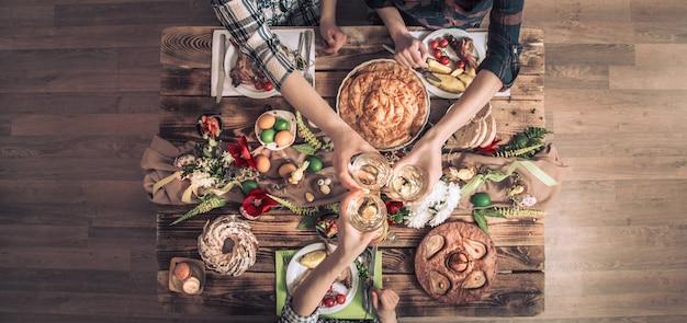 Amis de vacances ou famille à la table de fête avec viande de lapin, légumes, tartes, œufs, vue de dessus.