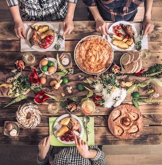 Amis de vacances ou famille à la table des fêtes avec viande de lapin, légumes, tartes, œufs, vue de dessus.