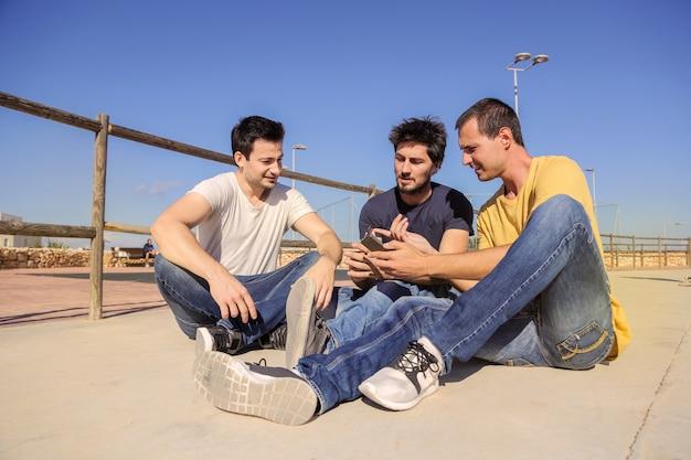Amis vérifiant un smartphone en plein air