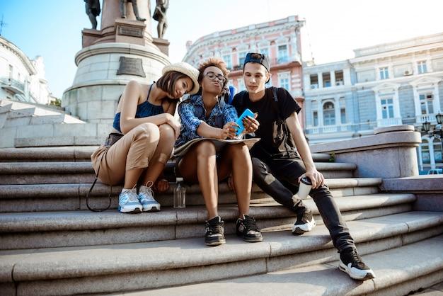 Amis voyageurs avec des sacs à dos souriant, faisant selfie, assis près de la vue.