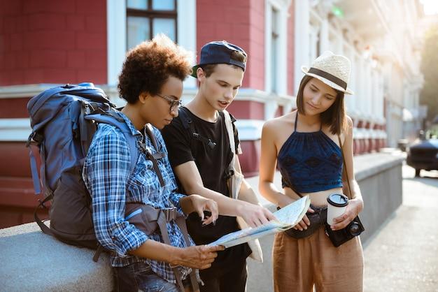 Amis voyageurs avec des sacs à dos souriant, à la recherche d'itinéraire à la carte dans la rue.