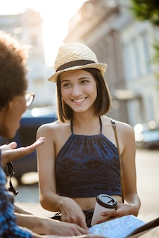 Amis voyageurs souriant, parlant, tenant la carte à l'extérieur.