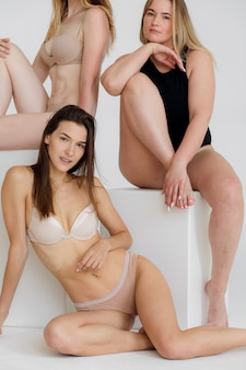 Amitié beauté corps positif et personnes concept groupe de femmes heureuses différentes en sous-vêtements blancs sur fond rose photo de haute qualité
