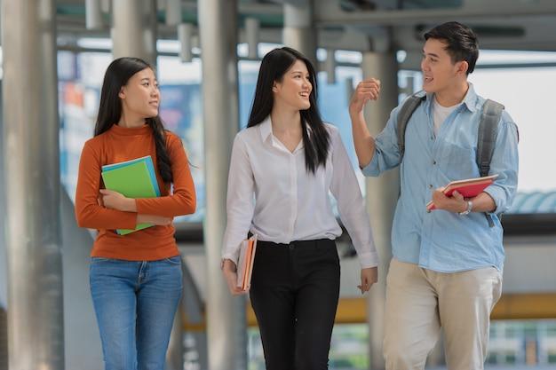 Amitié sur le campus, les étudiants avec des livres passent du temps ensemble.