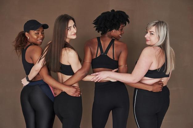 Amitié entre jeunes et adultes. groupe de femmes multiethniques debout contre l'espace brun