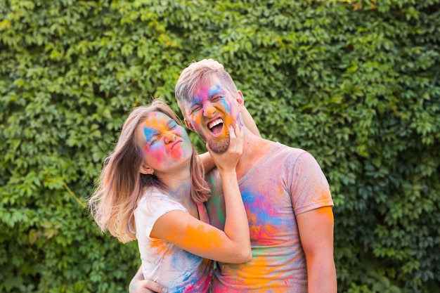 Amitié, festival de holi, concept de personnes - jeune couple jouant avec les couleurs au festival de holi.