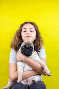 L'amour des animaux. adolescente bouclée embrasse son chien carlin triste avec amour