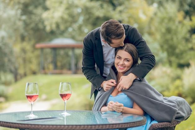 Amour, attention. jeune homme adulte en costume sombre avec plaid couvrant soigneusement heureux jolie femme assise dans un café sur la nature