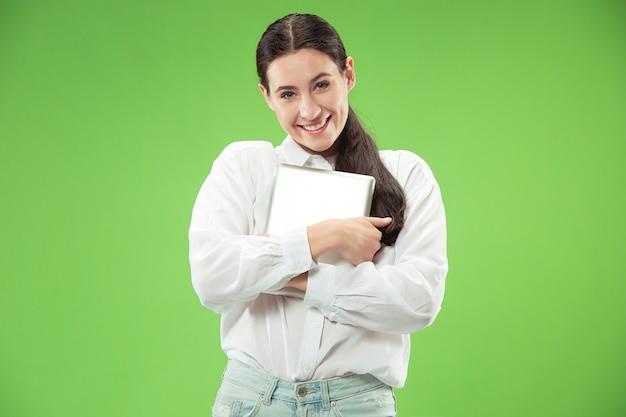 Amour au concept informatique. attractive portrait avant femme demi-longueur, mur vert à la mode. jeune femme jolie émotionnelle. émotions humaines, expression faciale
