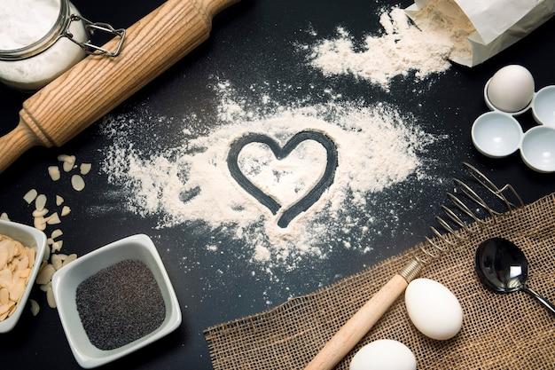 L'amour au four. fond de boulangerie. ingrédients de cuisson et ustensiles de cuisine sur fond noir. farine, noix d'amande, oeufs. vue de dessus, mise à plat. composition de cuisine moderne.
