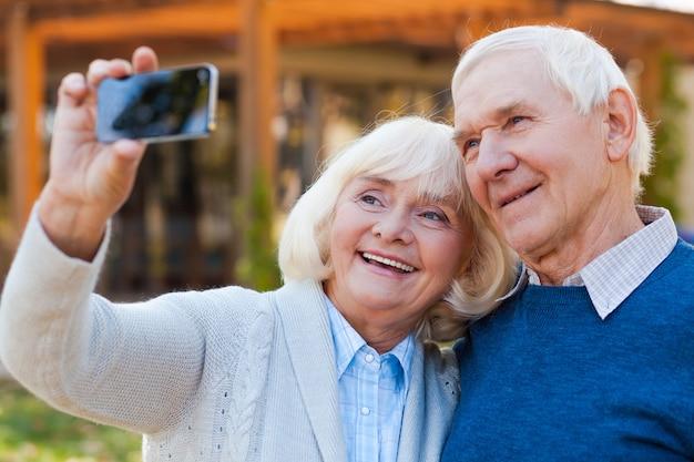 L'amour au point. heureux couple de personnes âgées se liant et faisant un selfie tout en se tenant à l'extérieur