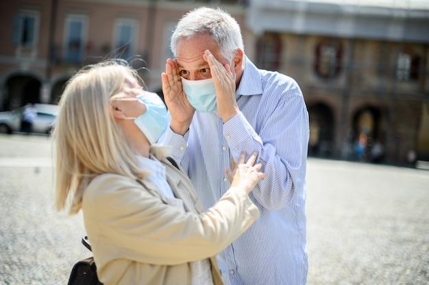 L'amour au temps du coronavirus. couples aînés, étreindre, extérieur, porter, masques