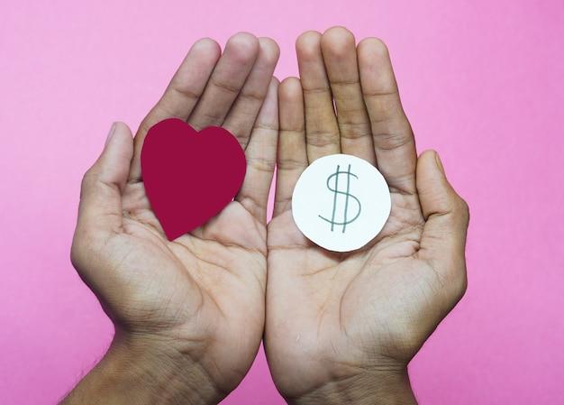 L'amour a besoin d'argent concept coeur en main dollors choisissent l'amour ou l'argent