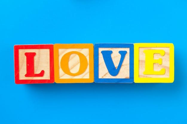 Amour. blocs d'alphabet coloré en bois sur bleu