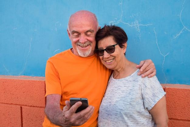 Amour et complicité pour un couple de personnes âgées regardant ensemble le même téléphone portable. sourires et moment de détente. couleur orange et bleu clair
