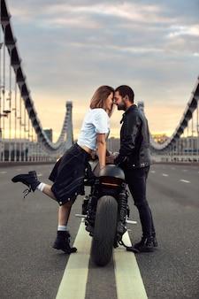 Amour et concept romantique. beau couple en moto se dresse face à face au milieu de la route
