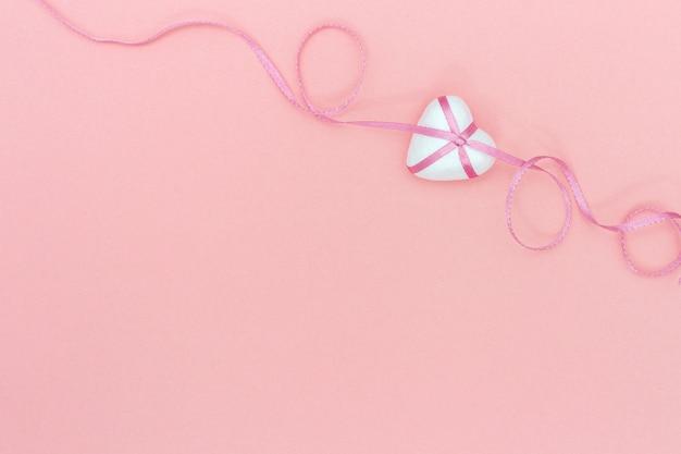 Amour concept de vacances romantiques pour le mariage ou la saint-valentin. joli coeur avec ruban de ruban rose sur fond de papier rose avec espace de copie. mise à plat