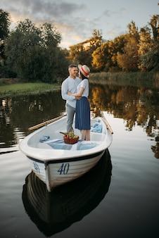 Amour couple debout dans un bateau sur un lac calme au jour d'été au coucher du soleil. rencontre romantique, balade en bateau, homme et femme marchant le long du lac