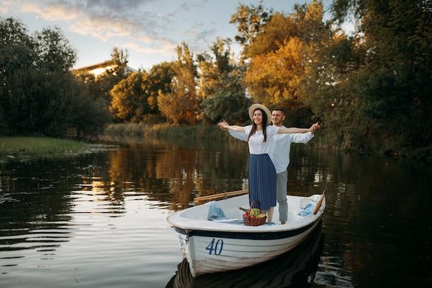 Amour couple debout dans un bateau sur un lac calme au jour d'été au coucher du soleil. rencontre romantique, balade en bateau, homme et femme marchant le long de la rivière