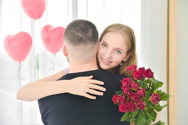 Amour couple donnant une fleur rose dans le bonheur de la chambre dans le concept de la saint-valentin amoureuse